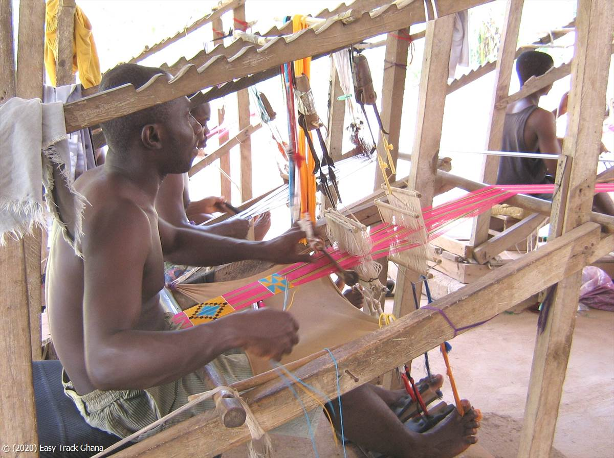 Weaving Kente on a hand made loom in the Kente village of Adanwomase, Ghana
